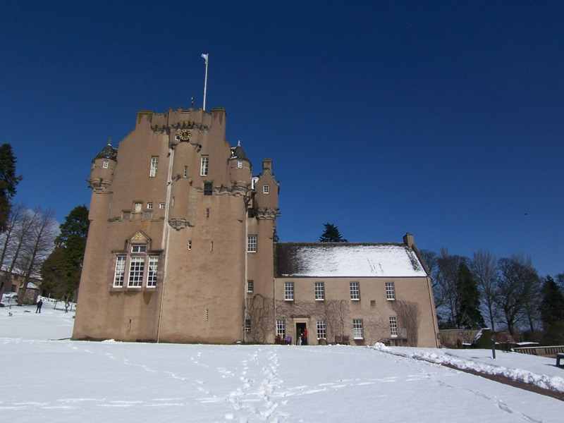 Crathes Castle with snow and blue skies